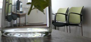 Einrichtung des Wartebereichs mit Stühlen, Kaltgetränken und Kaffeemaschine im Hintergrund.