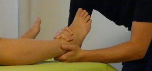 Behandlungsbeispiel am Fußgelenk, die Hände des Therapeuten greifen den Fuß der Patientin.